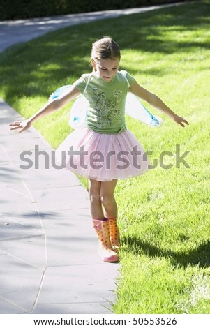 Girl wearing fairy wings and tutu balancing on edge of path, portrait - stock photo