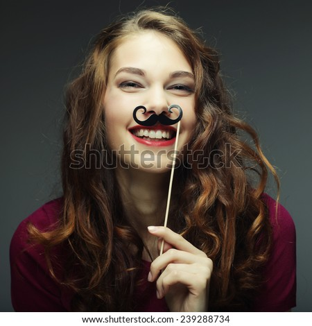 Girl wearing fake mustaches. Ready for party. - stock photo
