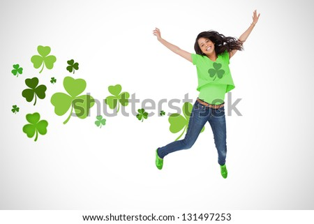 Girl wearing green shamrock t-shirt jumping for joy on shamrock background