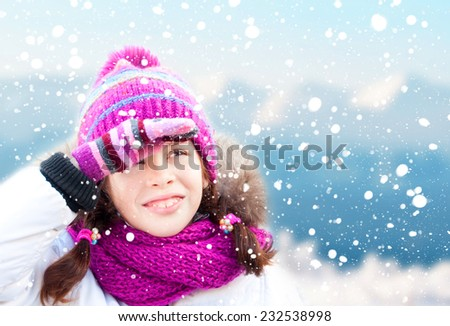 Girl wearing hat, scarf and mittens looking at snow - stock photo