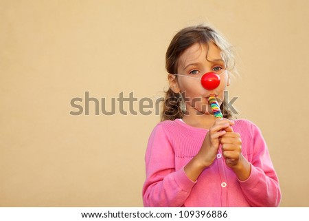 Girl wearing pink blouse with red clown nose sucks multicolored candies.