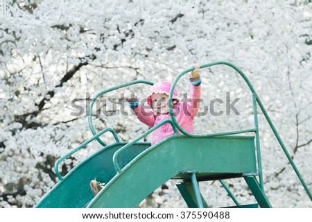 Girl wearing pink jacket and waving her hand is sliding down old playground slide  - stock photo