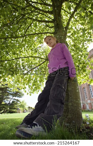 Girl wearing purple top and combat trousers, leaning against tree trunk in garden, head cocked, portrait, low angle view