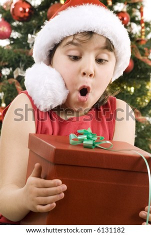 girl wearing santa hat with a gift, blurred decorated tree as background - stock photo