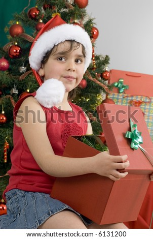 girl wearing santa hat with a gift, blurred decorated tree as background