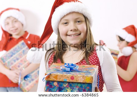 girl wearing santa hat with a gift, there are some kids in the background