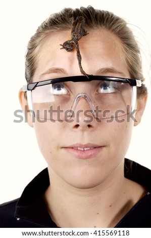 Girl wearing science class goggles with a brown tree frog climbing on her face