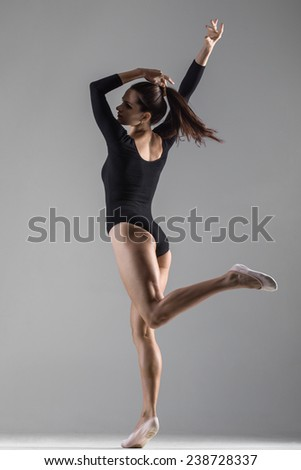 Girl wearing sport body and pointe shoes is dancing