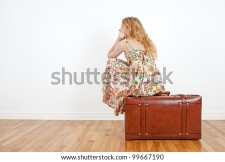 Girl wearing summer dress sits on a vintage suitcase, anticipating travel and waiting. - stock photo