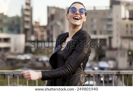 Girl wearing sunglasses laughing in the city