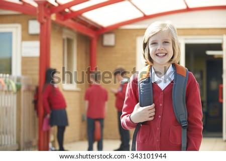 Girl Wearing Uniform Standing In School Playground - stock photo