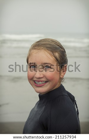 Girl wearing wet suit just out of water dripping wet on Rockaway beach Oregon - stock photo