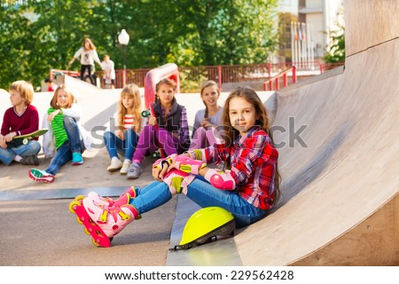 Girl wears in-line skates sits in front with mates