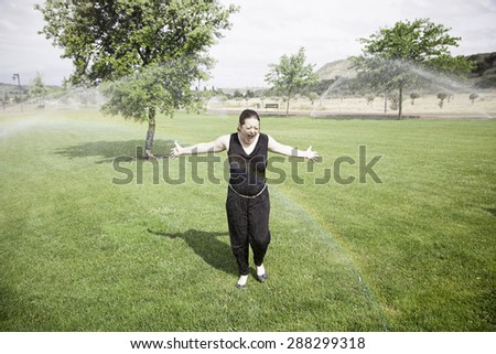 Girl wet water sprinkler garden, nature