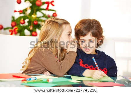 Girl whispering a wish in the ear of a boy at christmas - stock photo