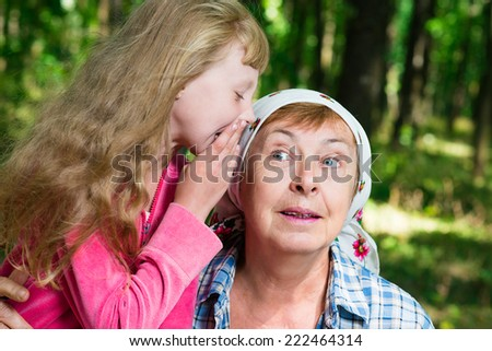 girl whispers to her grandmother's ear - stock photo