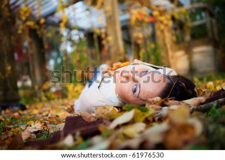 Girl who is laying on leafs - stock photo