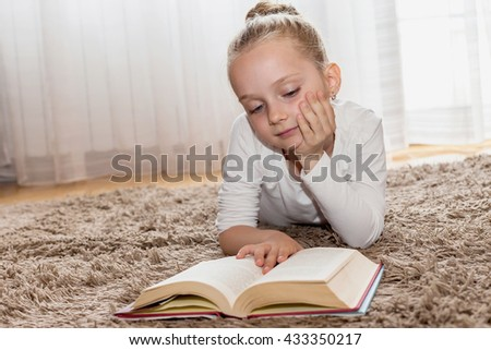 Girl who reads a book on living room floor