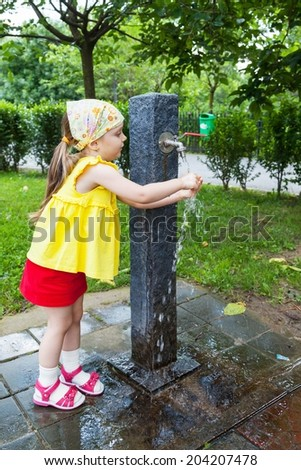 Girl who wash their hands at a fountain in the park - stock photo