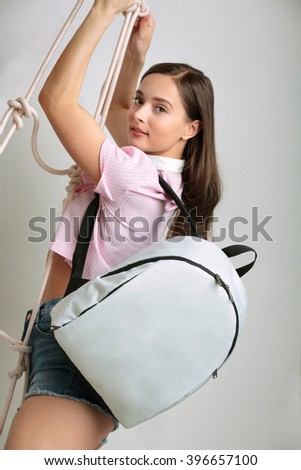 girl with a backpack on a rope ladder at the studio - stock photo