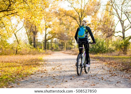 girl with a backpack riding a bicycle in a park. Back view