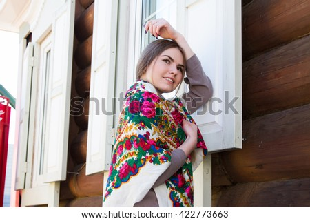 Girl with a bandana against the background of a wooden house