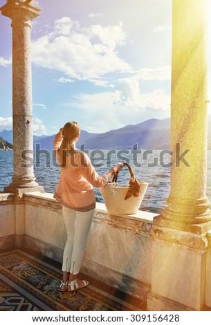 Girl with a basket bag at the Como lake, Italy - stock photo