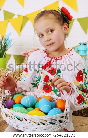 Girl with a basket of colored eggs