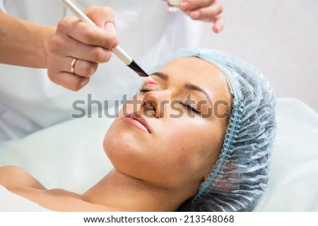 Girl with a beautician at spa salon. Beautician performs cosmetic procedures.applying cosmetic cream by brush. Cosmetology, facial, beauty - The concept of facial skin care. Article about cosmetology.