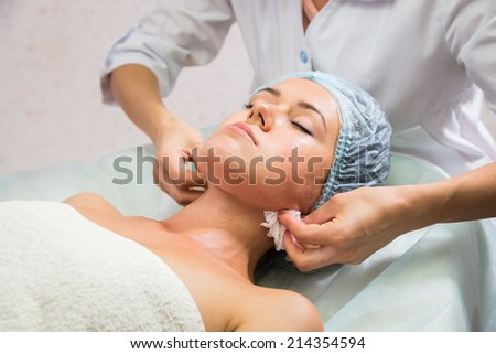Girl with a beautician at spa salon. Beautician performs cosmetic procedures.applying cosmetic cream by brush. Cosmetology, facial, beauty - The concept of facial skin care. Article about cosmetology. - stock photo