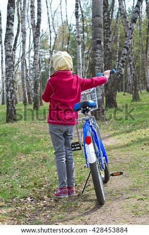 girl with a bicycle in the woods - stock photo