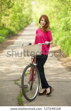 Girl with a bike in the countryside alley