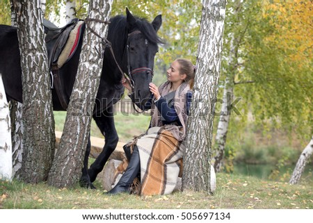 girl with a black horse in the autumn under birch.
