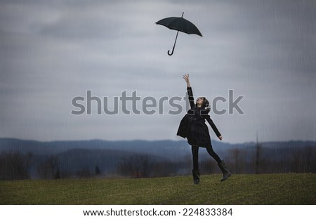 girl with a black umbrella in the rain - stock photo