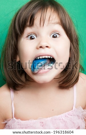 Girl with a blue tongue on food dyes - stock photo