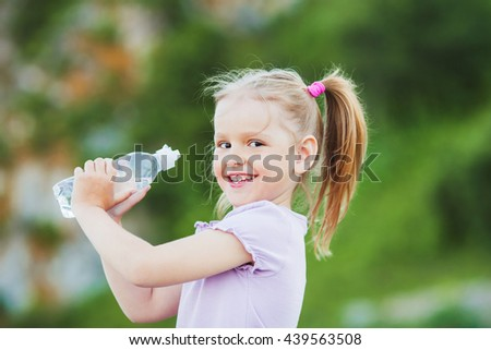 Girl with a bottle with water, outdoor