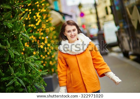 Girl with a brightly decorated Christmas tree in Paris - stock photo