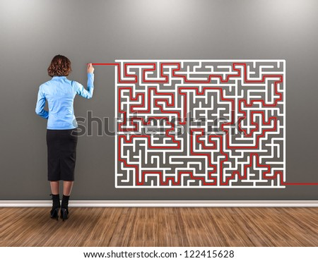 Girl with a brush in a hand draws a way from a labyrinth - stock photo