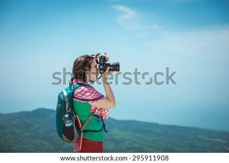 girl with a camera on top of a mountain .