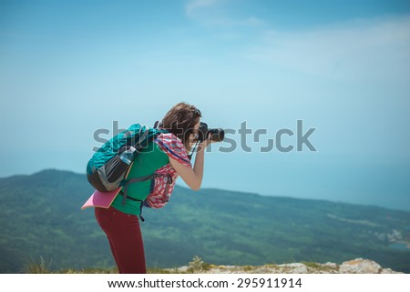 girl with a camera on top of a mountain . - stock photo