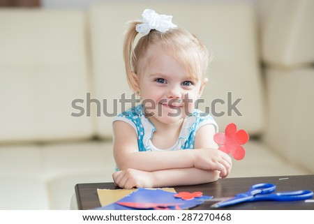 girl with a cardboard cut out of a red flower looking into the camera and smiling - stock photo