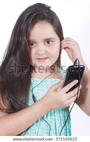 Girl with a cell in the hands inserted into the ear earphone