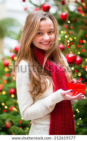 Girl with a Christmas present near the Christmas tree