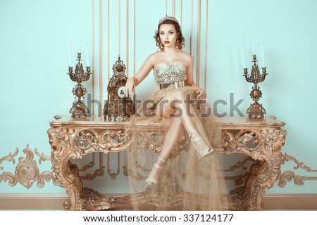 Girl with a crown on his head sitting on an old table.  Her fashion image of the queen.