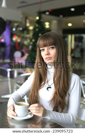 Girl with a cup of coffee in a shopping center on the background of the Christmas tree