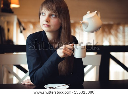 Girl with a cup of tea in the cafe. Levitation, kettle hangs in the air - stock photo
