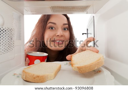 Girl with a cup  takes tost from a microwave - stock photo