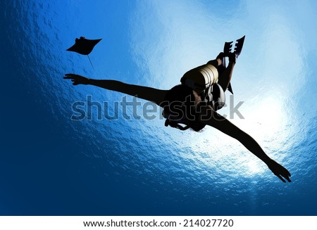 Girl with a diving under the water on a blue background. - stock photo