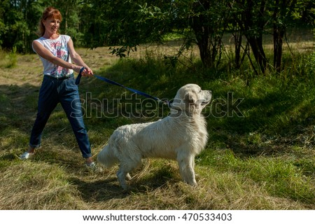 girl with a dog breed of retriever on a leash