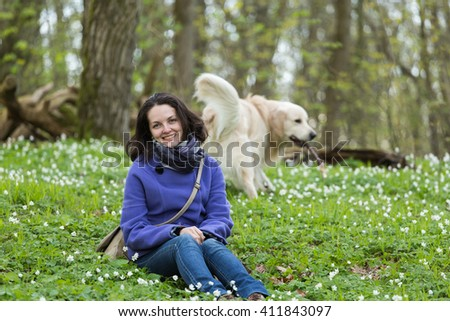 girl with a dog golden retriever in the flowers of the forest